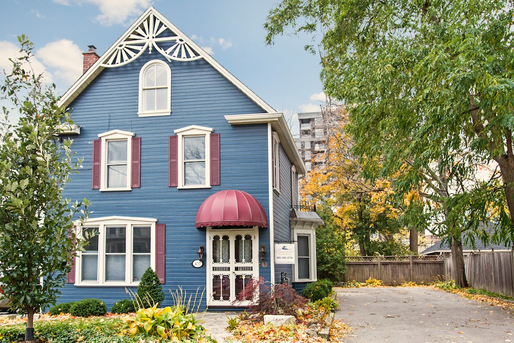 Downtown Burlington century home with gingerbread details and restored blue clapboard siding.