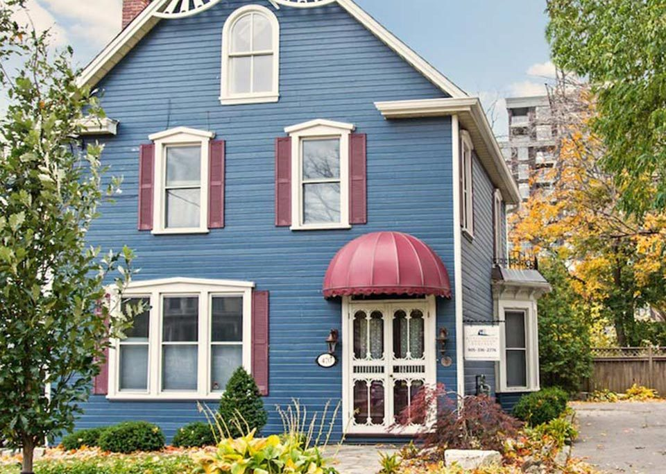Downtown Burlington century home rental with gingerbread details and restored blue clapboard siding.